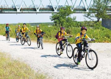 常願寺川左岸の河川敷を自転車で走る子どもたち