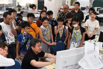 編集局を見学し、社員から紙面制作の手順などの説明を受ける参加者=13日、熊本市中央区の熊日本社(上杉勇太)