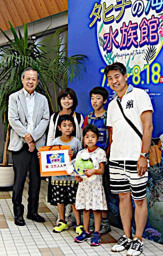 衣笠理事長(左)から記念品を贈られ、笑顔の八幡さんたち=13日、境港市のSANKO夢みなとタワー