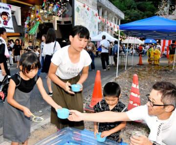 鹿野川夏まつりで、被災家屋を解体した跡地に設けられたスーパーボールすくいを楽しむ子どもたち=11日夕、大洲市肱川町山鳥坂