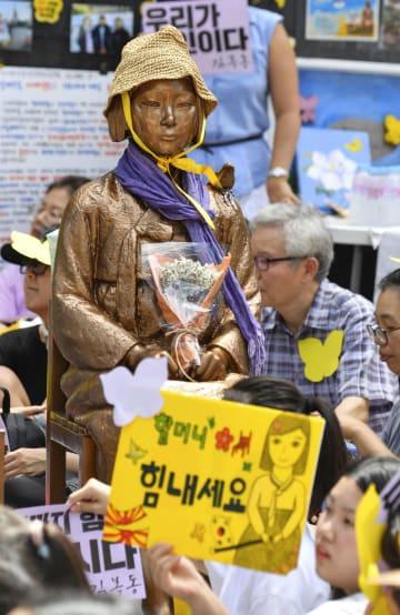 14日、ソウルの日本大使館前で開かれた従軍慰安婦問題の抗議集会と少女像(共同)
