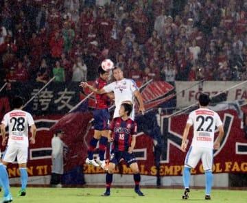 激しい雨の中、激戦を繰り広げるファジアーノ岡山(赤いユニホーム)と川崎の選手=シティライトスタジアム