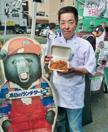 当時の店先にあったクマの看板と一緒に小澤さん
