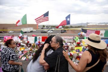 テキサス州エルパソで起きた銃乱射事件の現場に花をたむける人々(C)ロイター
