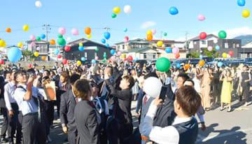 色とりどりの風船を飛ばす新成人=新庄市民文化会館
