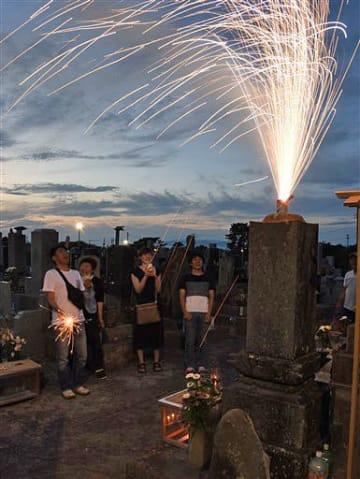 先祖代々の墓の上で噴出花火をする家族連れ