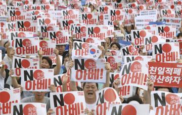 15日、ソウル中心部の光化門広場で「ノー安倍」と書かれたプラカードを掲げる集会参加者(共同)