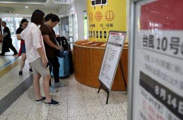 台風10号の影響で鉄道や空の便は始発から運転を見合わせた。JR宮崎駅では運行計画を確認する利用客らの姿がみられた=15日午前、宮崎市