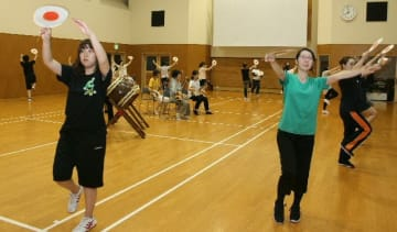大舞台に向けて練習し、うちわを持って一体感のある動きを見せる踊り子たち=豊後高田市美和の健康交流センター花いろ