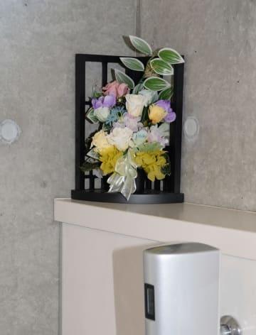 男子トイレの壁際の隅に置かれた造花=福井県小浜市川崎3丁目