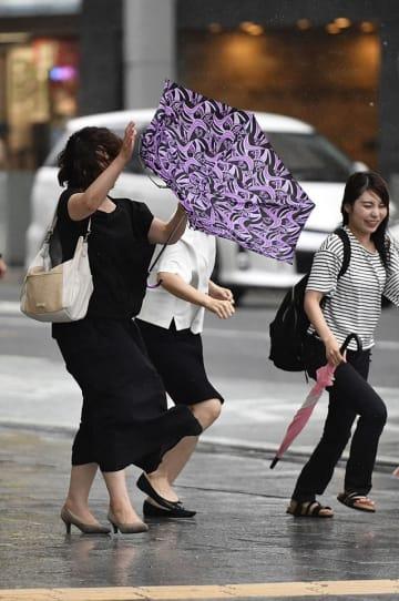台風10号の接近に伴う風雨の中を歩く人たち=15日午後4時16分、岐阜市神田町