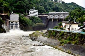 容量を確保するためトンネル洪水吐(左)から放流する鹿野川ダム=15日午後0時55分ごろ、大洲市肱川町宇和川