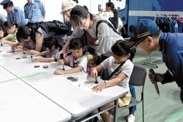 鑑識体験で指紋採取に挑戦する子どもたち=14日、さいたま市中央区のさいたまスーパーアリーナ