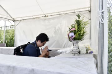 再設置された献花台で手を合わせる人たち=16日午前、京都市伏見区