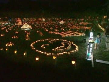 子どもたちを楽しませた「竹灯籠で迎え火を」。手前の灯籠は、節に二つの穴を開けて目とし、切り口が笑顔に見える=関川村土沢