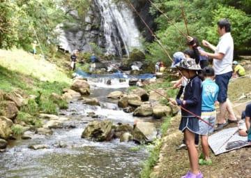 「平田川ちびっこつり大会」でニジマス釣りに挑む参加者たち