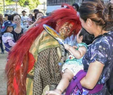 子どもを威嚇する赤い髪の鬼=16日、和歌山県九度山町