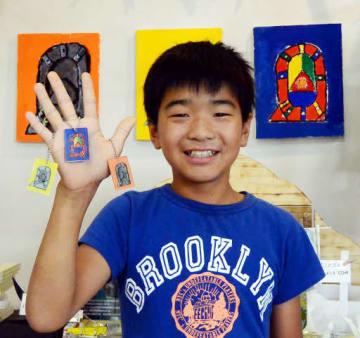 大好きなREを描いたキーホルダーを手にする小俣君。壁に掛かっているのが原画(石巻市のこども新聞の活動拠点)