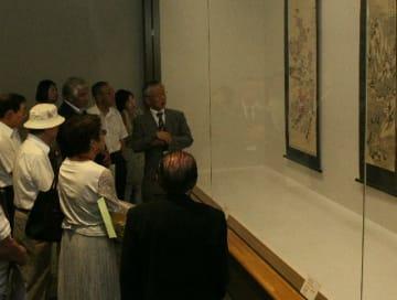 絵や作者の解説を聞きながら企画展を回る参加者=16日、宇佐市高森の県立歴史博物館