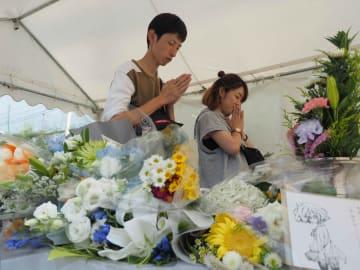 再設置された献花台で祈りをささげるファンら(16日午後5時3分、京都市伏見区)