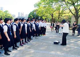 平和記念公園で合唱する豊浦中学校の3年生=今年4月、広島市