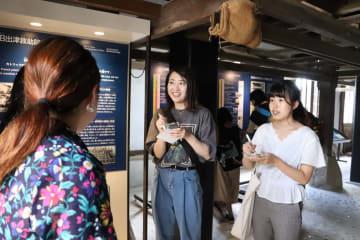 観光客(左)に外海に来て気付いたことや感想などを聞く学生たち=長崎市西出津町、旧出津救助院