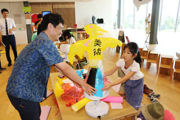 カラービニールで作った動物をサーキュレーターの上に置いて膨らませる親子=県美術館