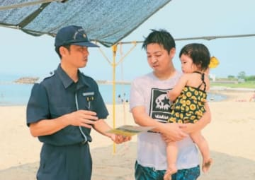海水浴客に啓発チラシを配り、安全意識の徹底を呼び掛ける大分海上保安部の保安官(左)=大分市神崎の田ノ浦ビーチ