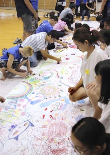 床に敷かれた紙に絵を描くイベント参加者ら=17日午後、神奈川県横須賀市