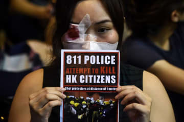 An anti-extradition bill protester holds a sign against police brutality during a gathering at Chater House Garden in Hong Kong on August 16, 2019. Photo: Lillian Suwanrumpha/AFP.