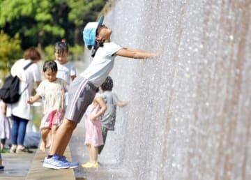 水族館前の壁面に流れる水に手を入れる女の子=17日午後、東京都江戸川区
