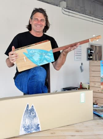 トロ箱ギターを手にする製作者のスティーブン・フォーク氏=阿久根市新町