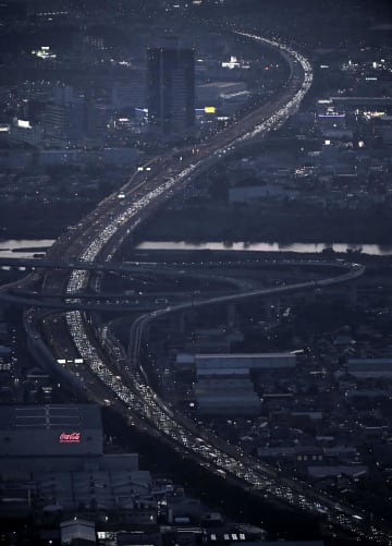 帰省先などからのUターンラッシュで東京方面(手前)に向かい渋滞する東名高速道路・海老名SA付近=17日午後6時48分、神奈川県海老名市(共同通信社ヘリから)