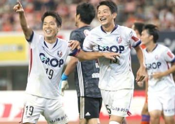 前半32分、先制ゴールを決め、歓声に応えるファジアーノ岡山の仲間隼斗(左)。右は移籍加入し初出場の山本大貴=デンカビッグスワンスタジアム