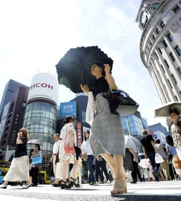 強い日差しが照りつける中、東京・銀座を行き交う人たち(C)共同通信社
