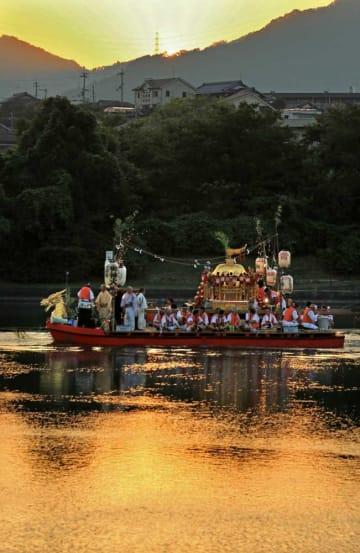 神輿を載せた御座船が夕日に染まる瀬田川を進む(17日午後6時20分、大津市・瀬田川)
