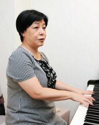 自宅のピアノの前でコンサートの練習をする原口佳代さん=宝塚市内