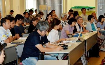 パネリストの活発な討論に聞き入るシンポジウム参加者=17日、那覇市おもろまち