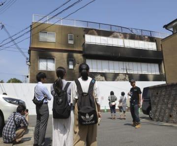 事件発生から1カ月となった「京都アニメーション」第1スタジオを訪れた人たち=18日午前、京都市伏見区