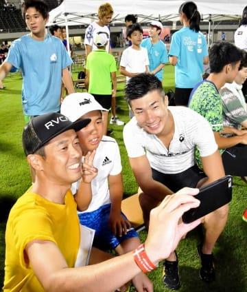一流選手たちのレースを間近で見た後、桐生祥秀選手(手前右)と記念写真に納まる観客=8月17日、福井県福井市の9.98スタジアム