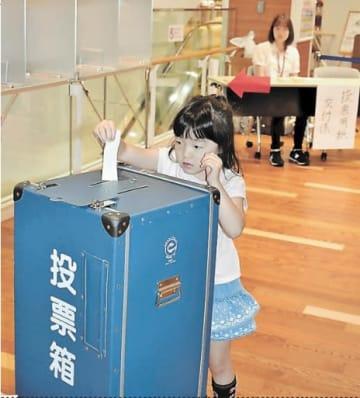 本物の投票箱に1票を入れる子ども。将来の有権者も参加できる