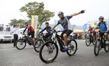 電動アシスト機能付きのマウンテンバイクを試乗する参加者=18日、熊本県阿蘇市
