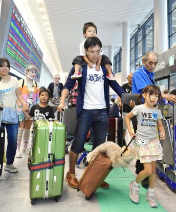 お盆休みを海外で過ごし、帰国した家族連れ=18日午後、成田空港