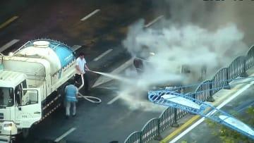 車が路上で突然炎上、通りかかった散水車が消防車に変身