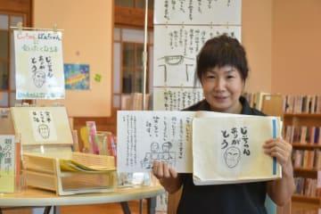 自らの体験をつづった絵日記を手に「認知症っていいものなんだよ」と伝える甲斐真由美さん=日向市