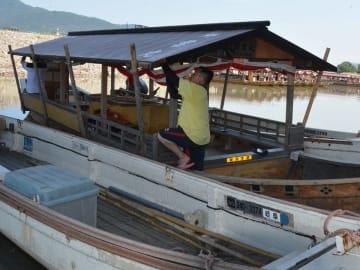 運航再開に向けて、台風で被害を受けた観覧船の屋根を修繕する船員=18日午前11時40分、岐阜市、長良川