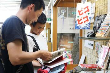 関連本を楽しそうに見る親子=佐賀市の県立図書館