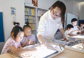 森さんの指導を受けながらサンドアートを楽しむ子どもたち