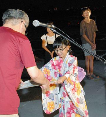 最優秀賞に選ばれ、表彰状を受け取る橋本さん=18日、鳥取市の千代河原市民スポーツ広場
