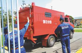 仲間の指示に従いながら車両を運転する消防団員